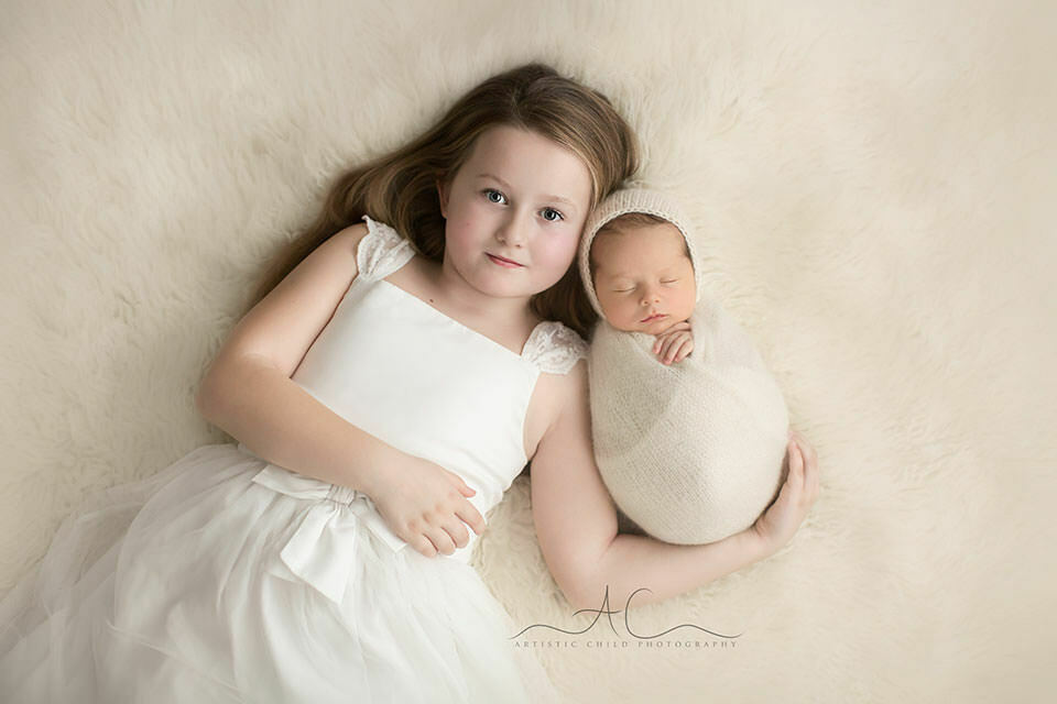 South East London Sibling Pictures | beautiful portrait of a 6 year old girl holding her newborn baby brother
