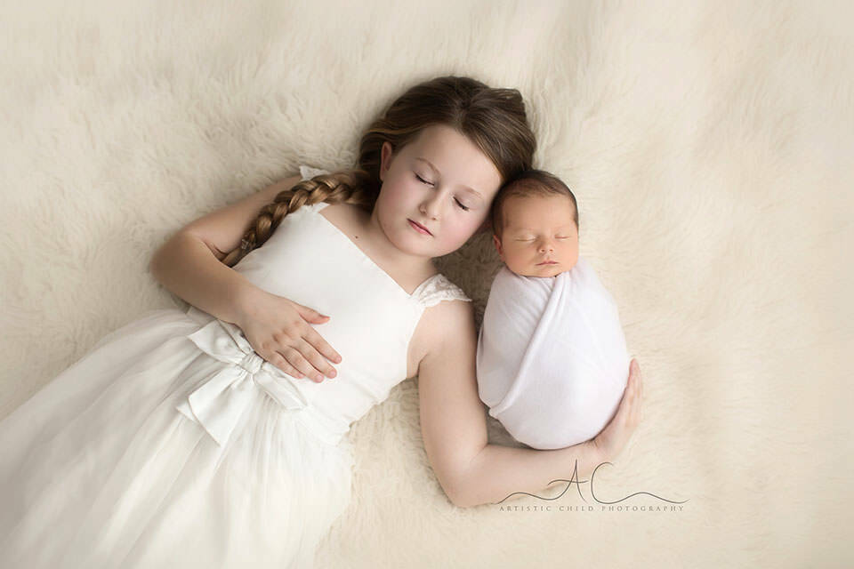 photo of a newborn baby boy and his older sister both having their eyes closed | London