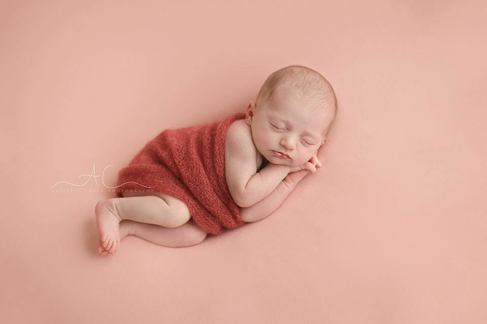Top London Newborn Portraits | newborn baby girl sleeps on her side under the hand knitted blanket