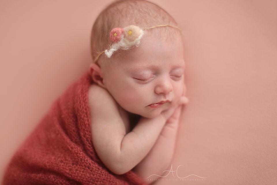 Top London Newborn Portraits | a close up photo of a newborn baby girl wearing a pretty pink tieback