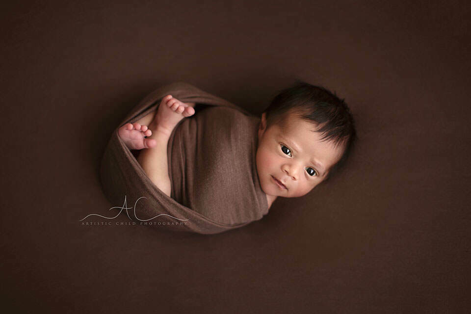 portrait of a swaddled awake newborn baby boy | London