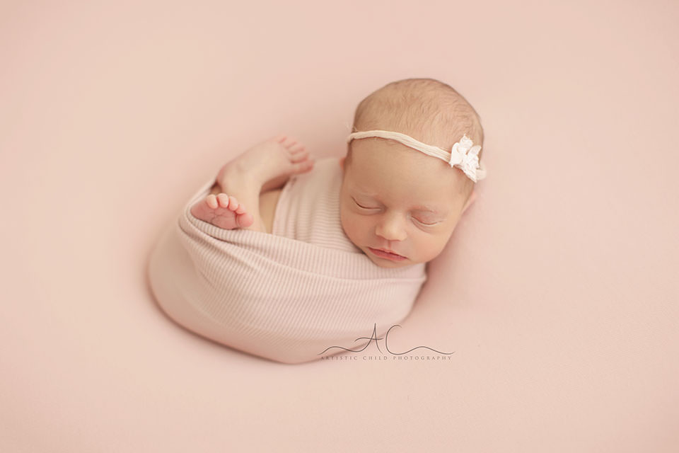 natural portrait of a newborn baby girl swaddled in a pink wrap | London