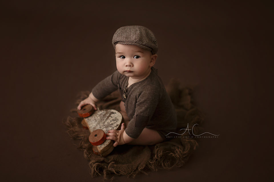 portrait of a 7 months old baby wearing a flat cap during a profesional photo session | London