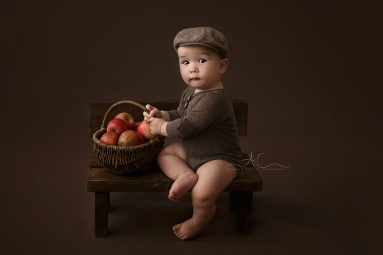 Bromley Baby Portraits | 7 months old baby boy sits on a small wooden bench and holds a wicker basket full of red apples