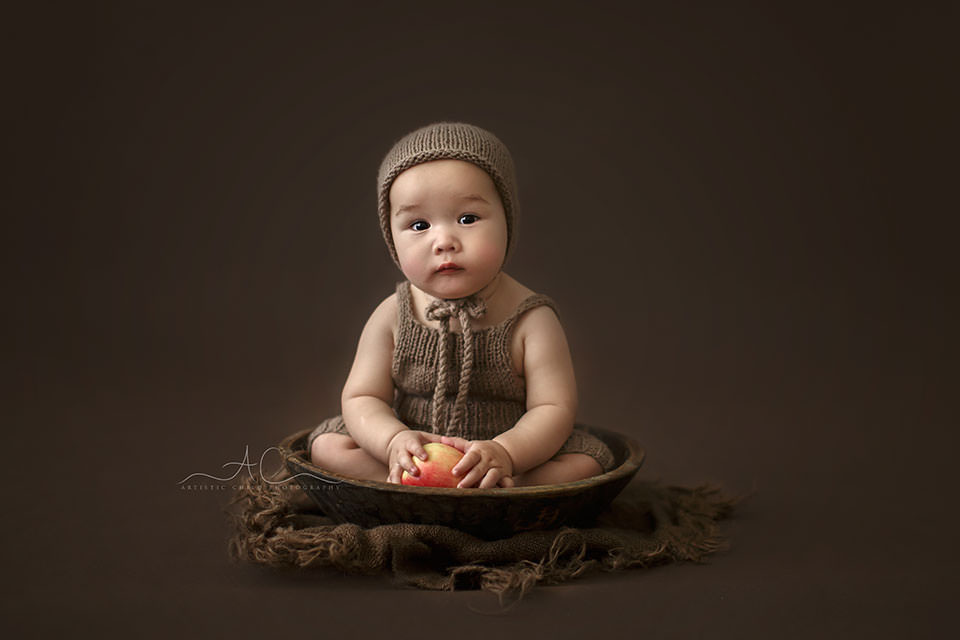 Bromley Baby Portraits | photo of a 7 months old baby boy sitting in a wooden bowl and holding a red apple