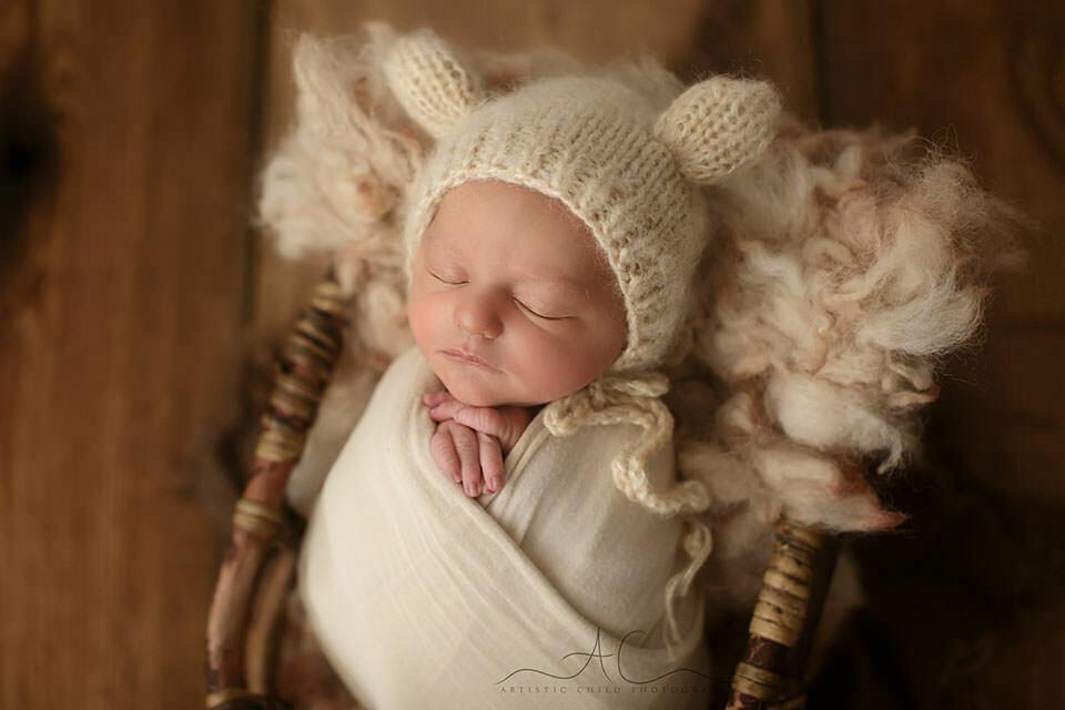 South East London Newborn Baby Boy Photography Offer | a backlit portrait of a newborn baby boy sleeping in a bamboo basket