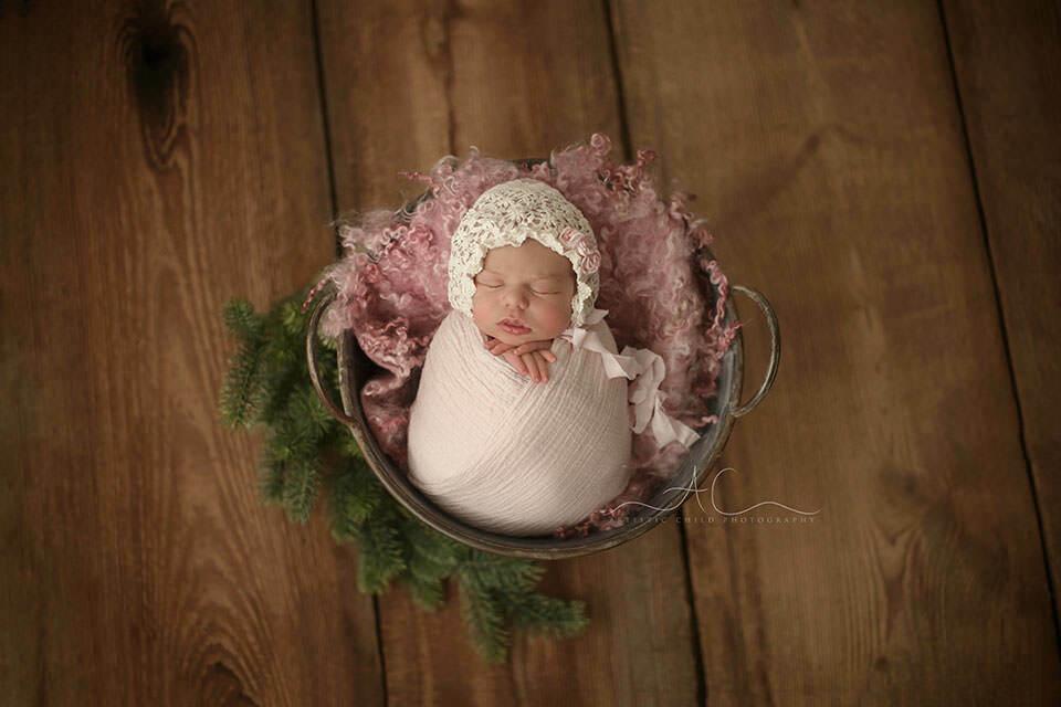 image of a newborn baby girl sleeping in a metal bucket prop | London
