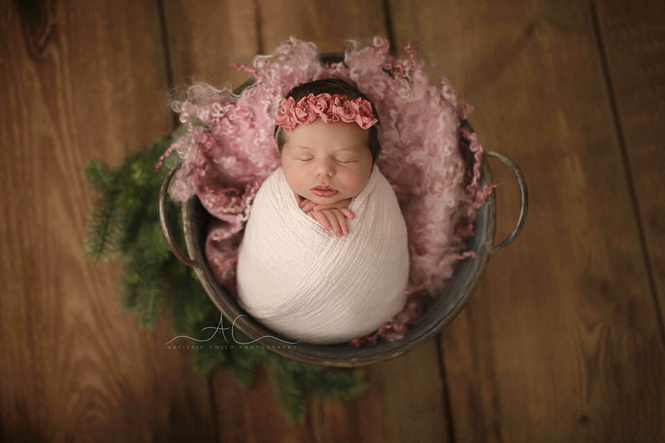image of a newborn baby girl sleeping in a metal bucket prop | London