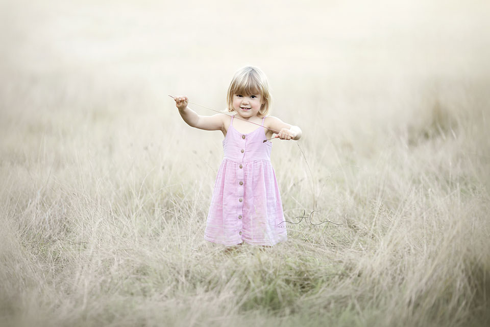 portrait of a 3 year old girl in a pink dress playing in the field of long dry grass | London