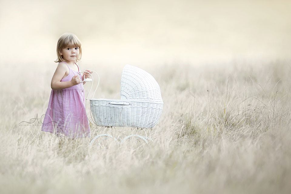 3 year old girl plays with a doll pram in the field of long dry grass | London