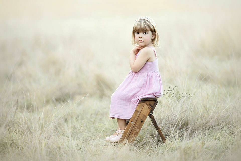 photo of a 3 year old girl sitting on a ledder steps in the filed of long dry grass | London