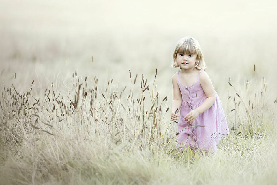 London Kids Pictures | portrait of a 3 year old girl taken in the field of dry long grass