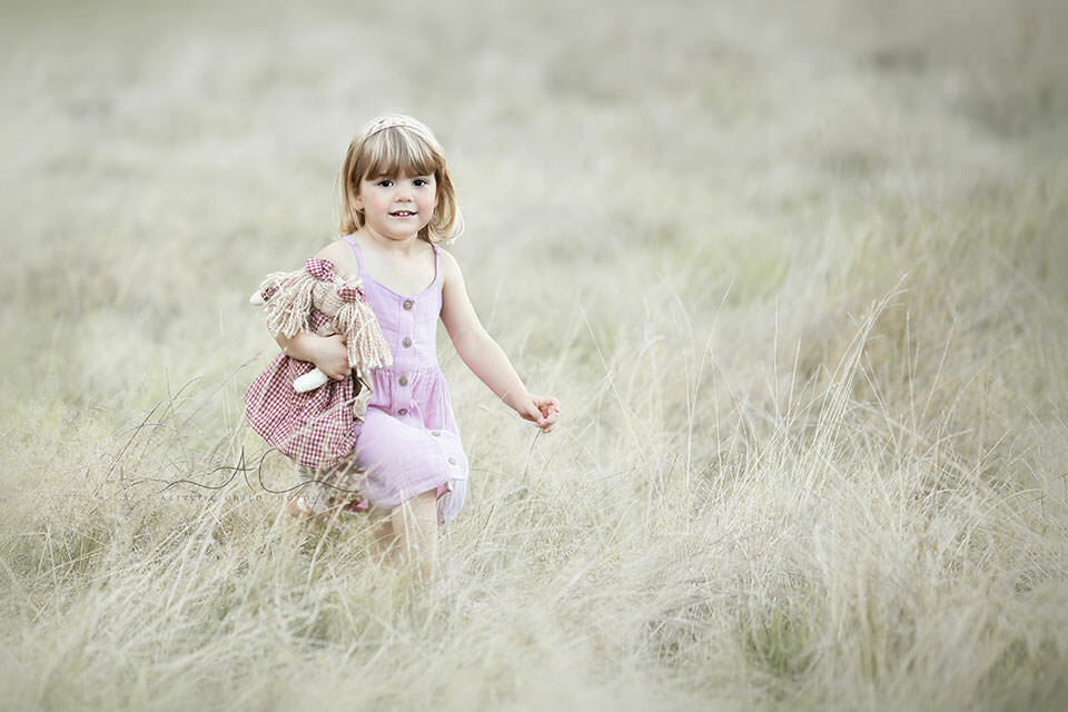 London Kids Pictures | 3 year old girl plays with the doll in the lond dry grass