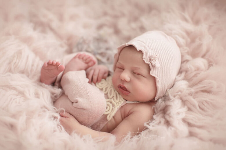 Professional Bromley Newborn Baby Photo Session   newborn baby girl photographed wearing a cute pink romper