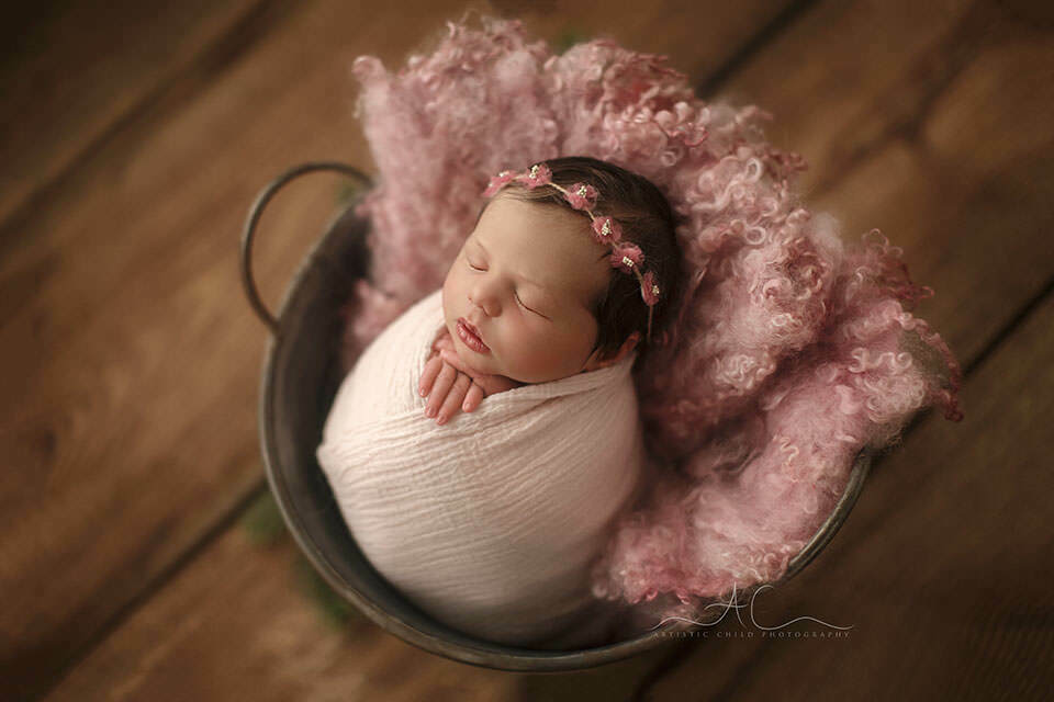 Professional Bromley Newborn Baby Photo Session | backlit portrait of a newborn baby girl sleeping in a bucket