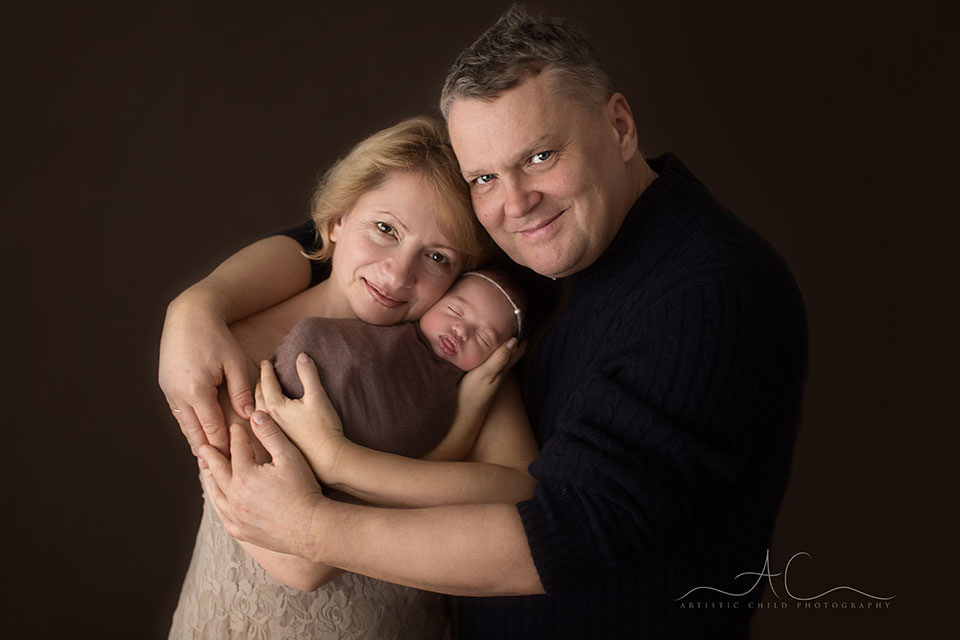 Professional South East London Family Photography Services | photo of grandparents holding their newborn grandaughter