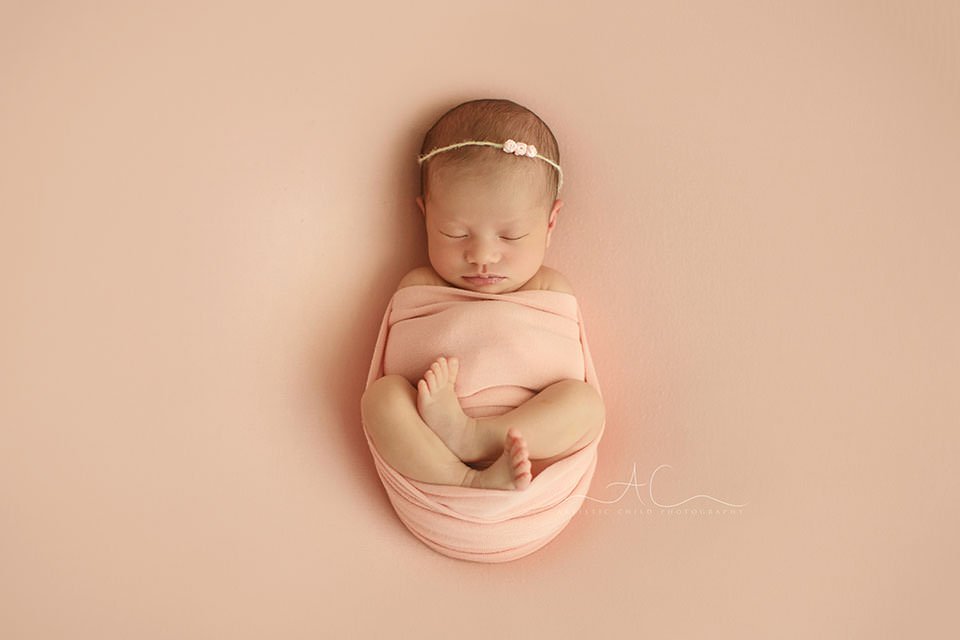 photo of a newborn baby girl swaddled in the pink wrap | London