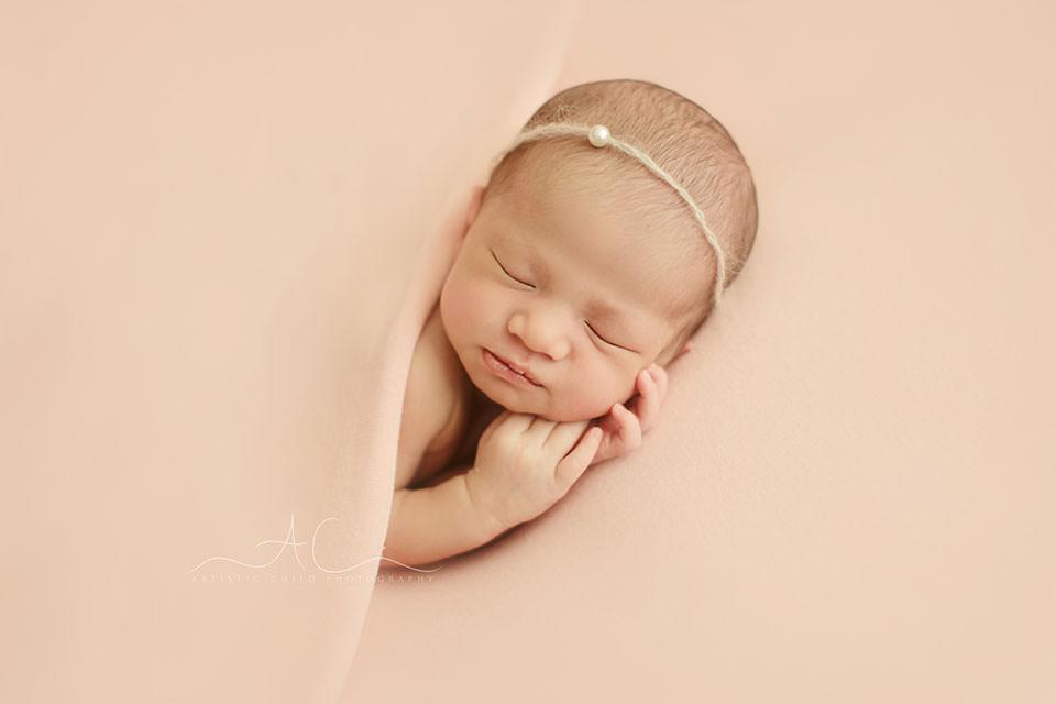 portrait of a newborn baby girl sleeping on side under a pink blanket | London
