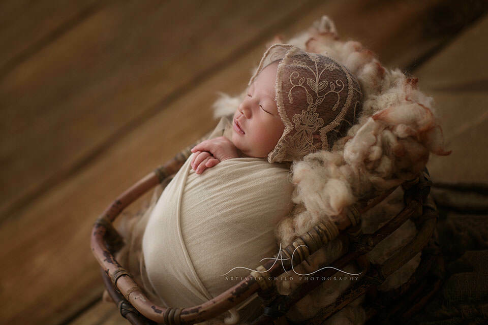 a backlit portrait of a newborn baby girl sleeping in a bamboo basket during her newborn photo session   London