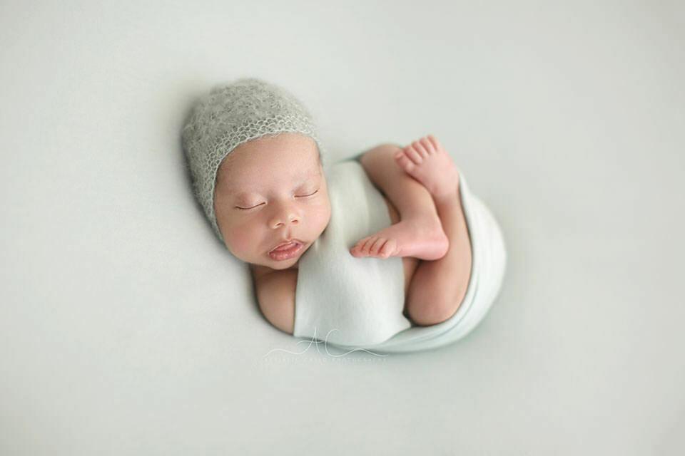portrait of a newborn baby boy wearing a hand knit blue hat | London