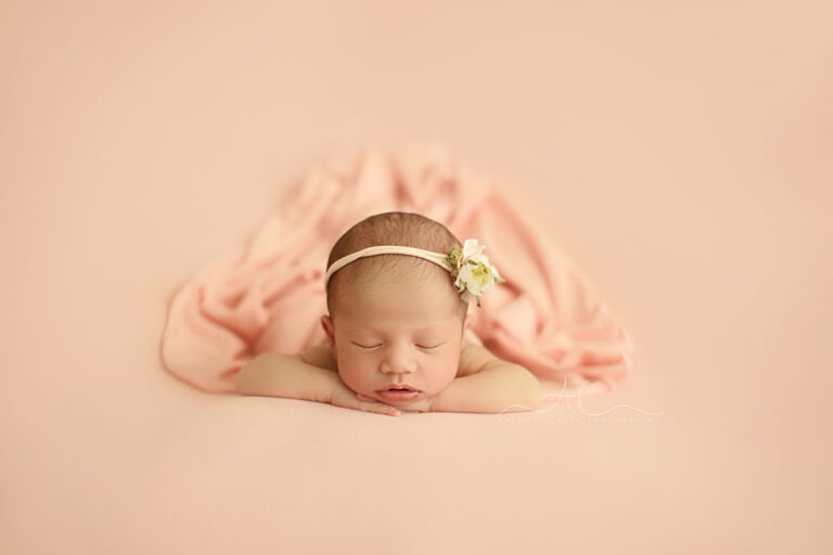 Bromley Newborn Baby Girl Photos   portrait of a newborn baby girl with a flower hairband sleeping in hands under chin position