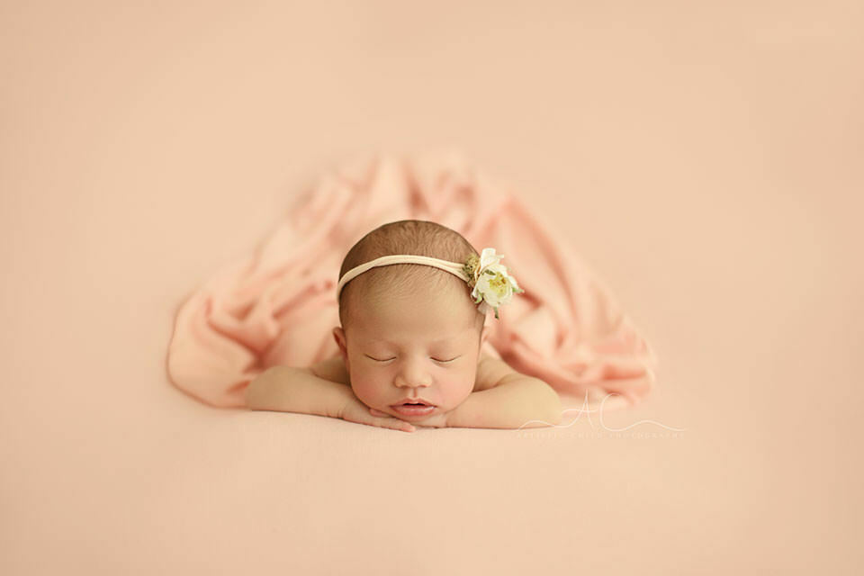 Bromley Newborn Baby Girl Photos | portrait of a newborn baby girl with a flower hairband sleeping in hands under chin position