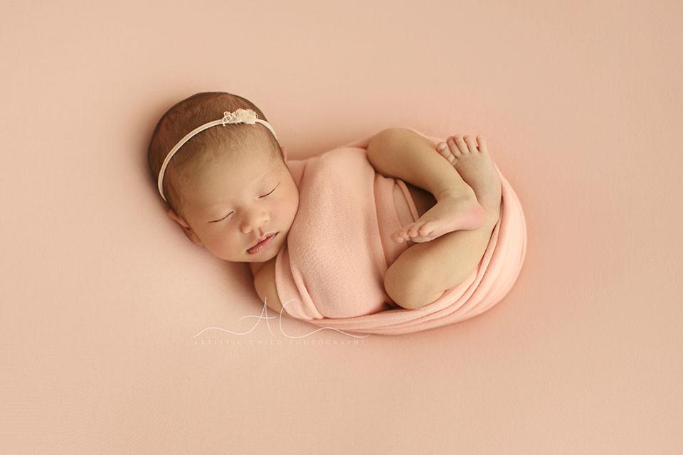 Bromley Newborn Baby Girl Photos | swaddled newborn baby girl sleeps on her back