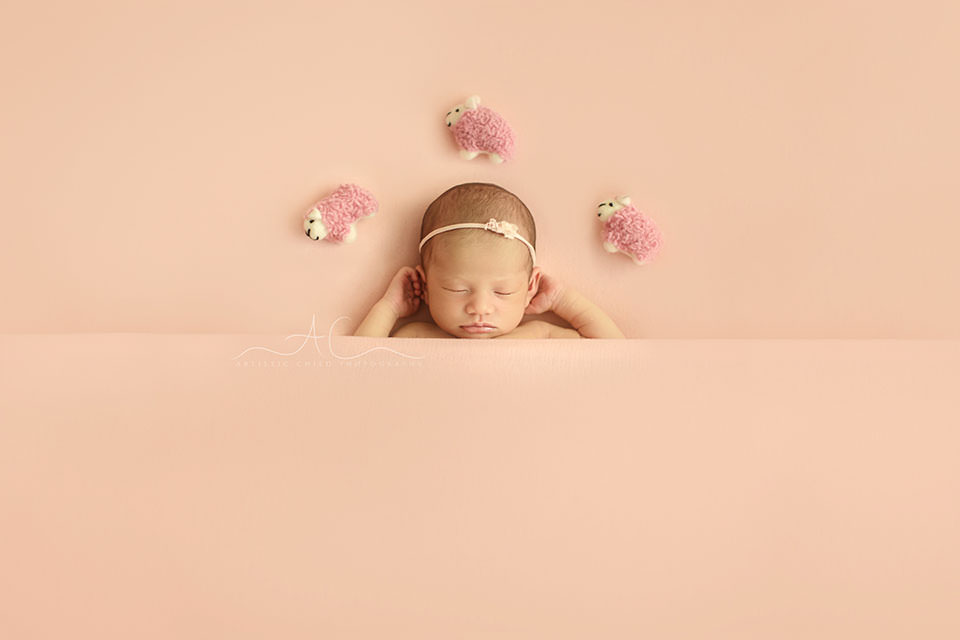 Bromley Newborn Baby Girl Photos | portrait of a newborn baby girl sleeping on her back and counting pink sheep above her head