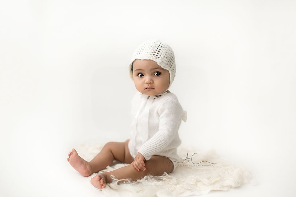 photo of a 7 months old baby girl wearing a pretty white bonnet   London