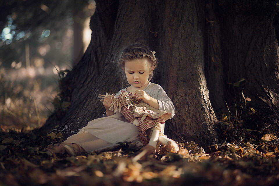outdoor portrait of a 3 year old girl who sits under a big tree and plays with a doll | London