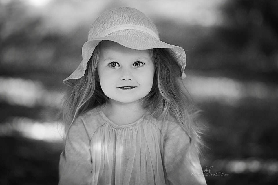 black & white outdoor portrait of a 3 year old girl wearing a straw hat | London