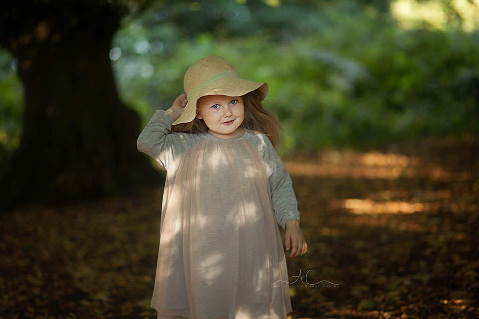 outdoor portrait of a 3 year old girl wearing a sun hat | London