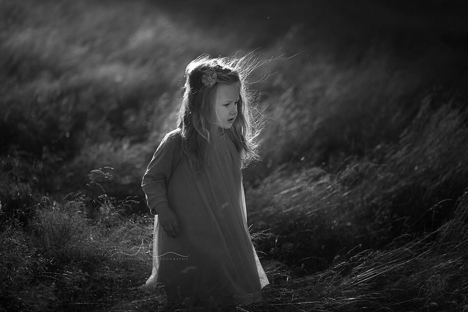 b&w portrait of a 3 year old girl playing in the long grass field | London