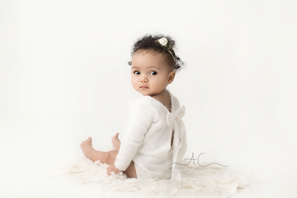 London Baby Girl Pictures | photo of 7 months old baby girl in a white cashmire romper with a bow at the back