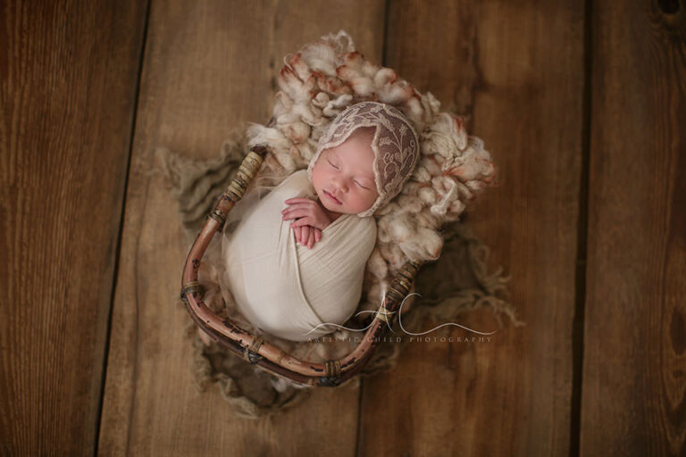 London Newborn Baby Girl Pictures   newborn baby girl sleeps in a bamboo basket during the newborn photo session