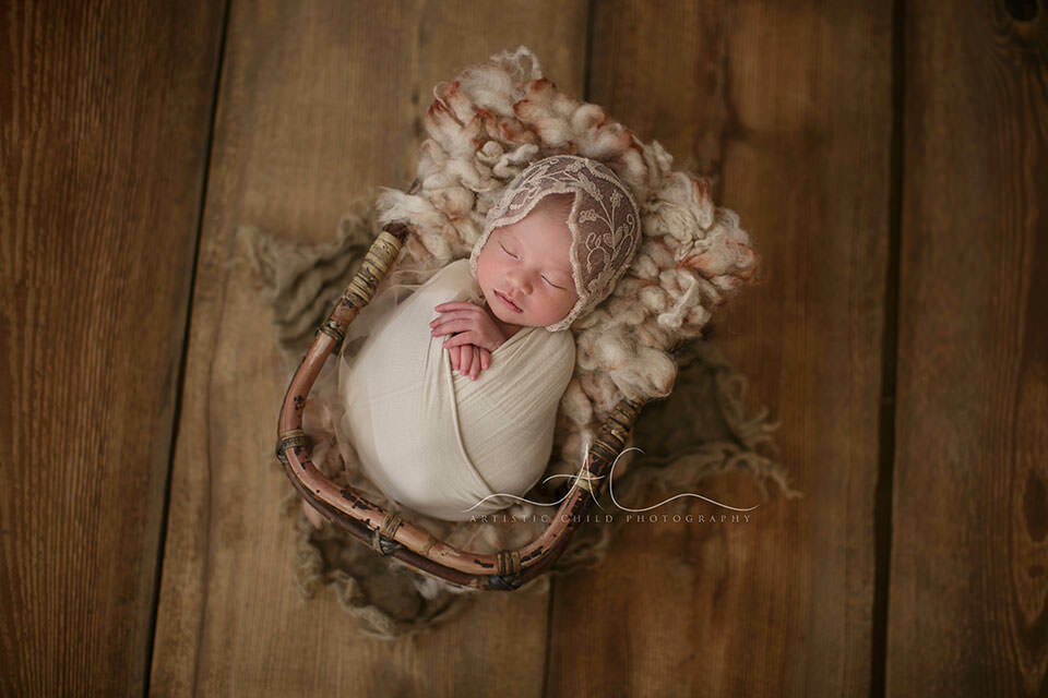 London Newborn Baby Girl Pictures | newborn baby girl sleeps in a bamboo basket during the newborn photo session