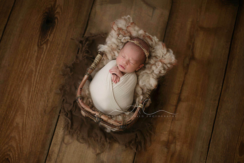 London Newborn Baby Girl Pictures   swaddled newborn baby girl sleeps in a bamboo basket