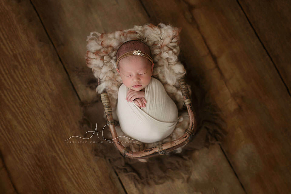 London Newborn Baby Girl Pictures   portrait of a newborn baby girl sleeping in a bamboo basket during a newborn photoshoot