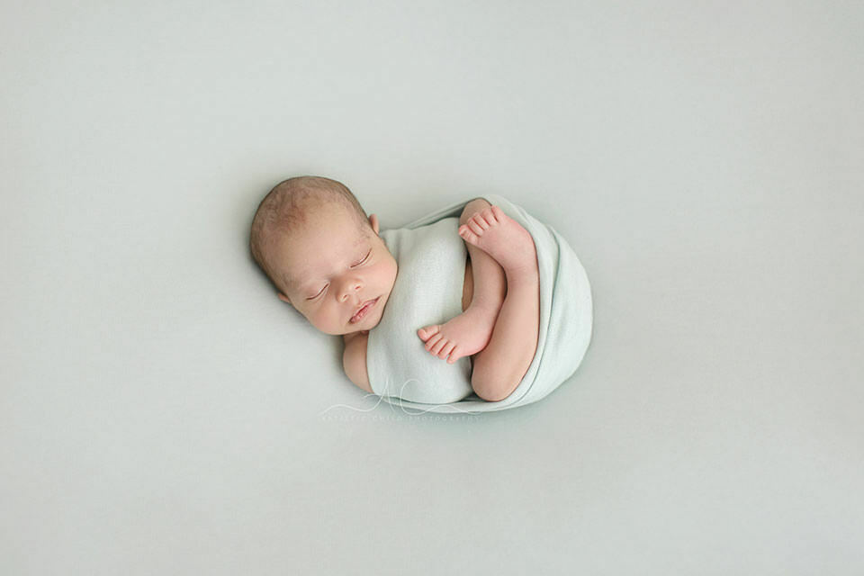 professional South East London newborn portraits | swaddled newborn baby boy photographed on a mint backdrop