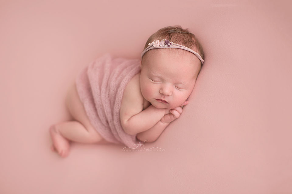 Awesome London Newborn Images | photo of a newborn baby girl wearing a pink headband