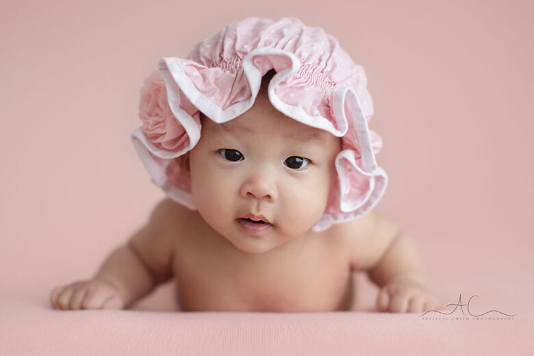 London 100 days celebration baby photos   portrait of a 3 months old baby girl wearing a cute pink hat