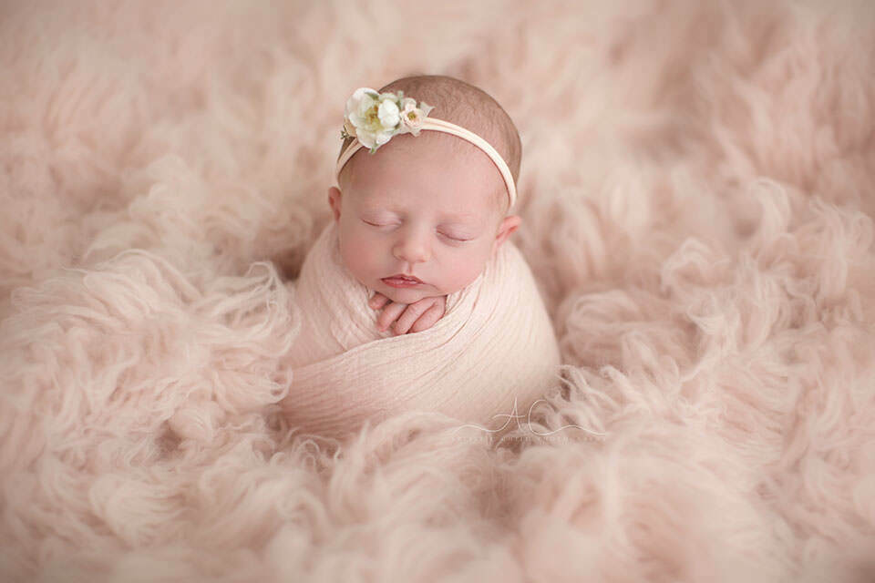 photo of a newborn baby girl wearing a beautiful flower tieback taken during professional photo session in London Bromley studio