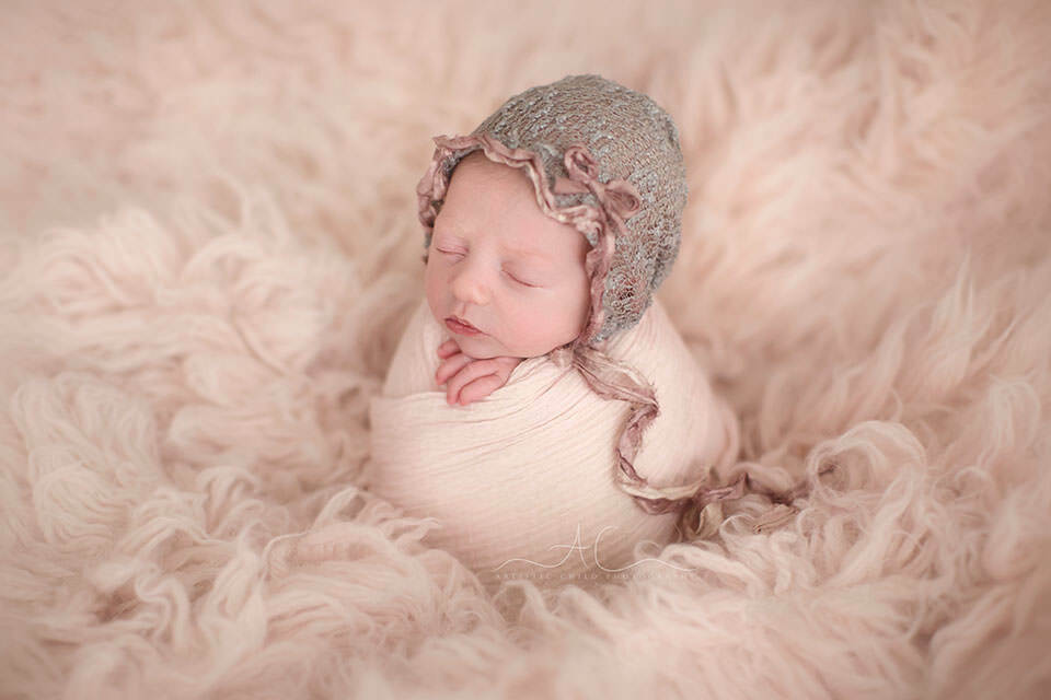 beautiful photo of a newborn baby girl wearing a cute bonnet during her newborn photo session in London Bromley studio