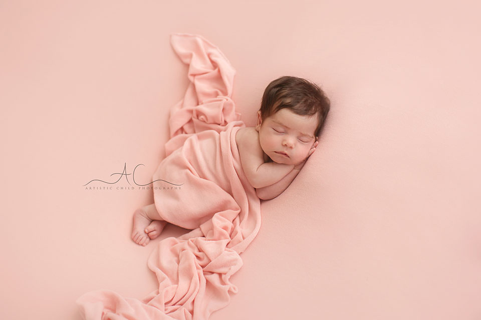 Professional Bromley Newborn Baby Photographer | newborn baby girl sleeps on her side during the newborn photo session and is covered by a pink throw.