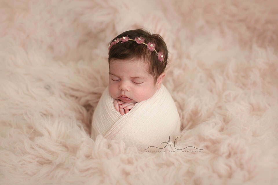 Professional Bromley Newborn Baby Photographer | portrait of a newborn baby girl with a pink flower tieback