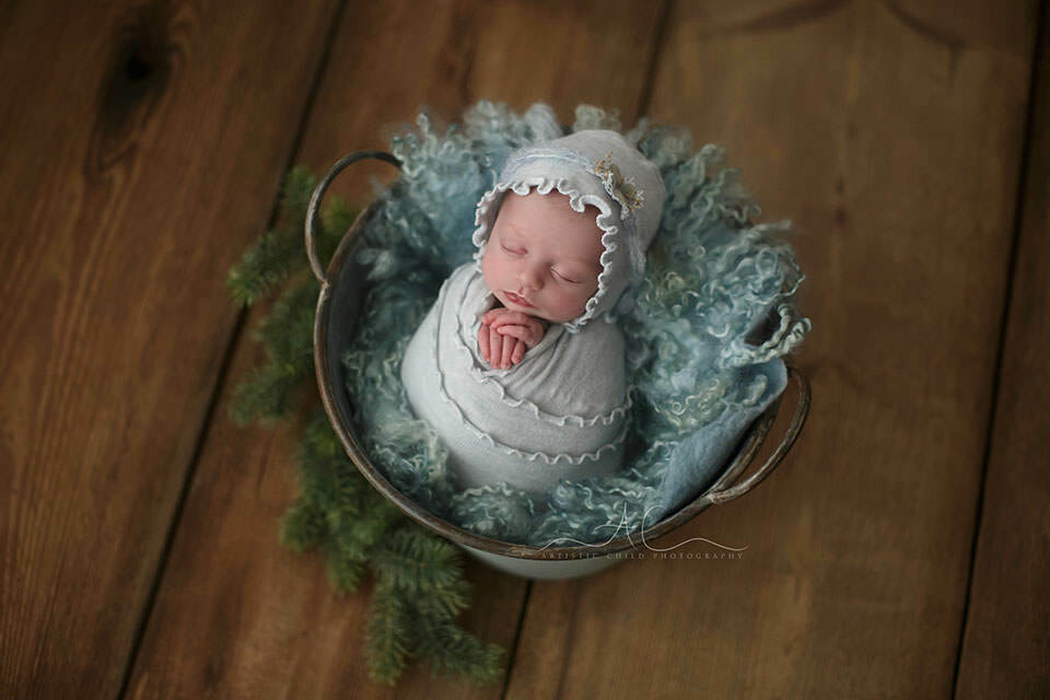 Professional Bromley Newborn Baby Pictures | stunning portrait of a newborn baby girl swaddled in a blue wrap and matching hat.