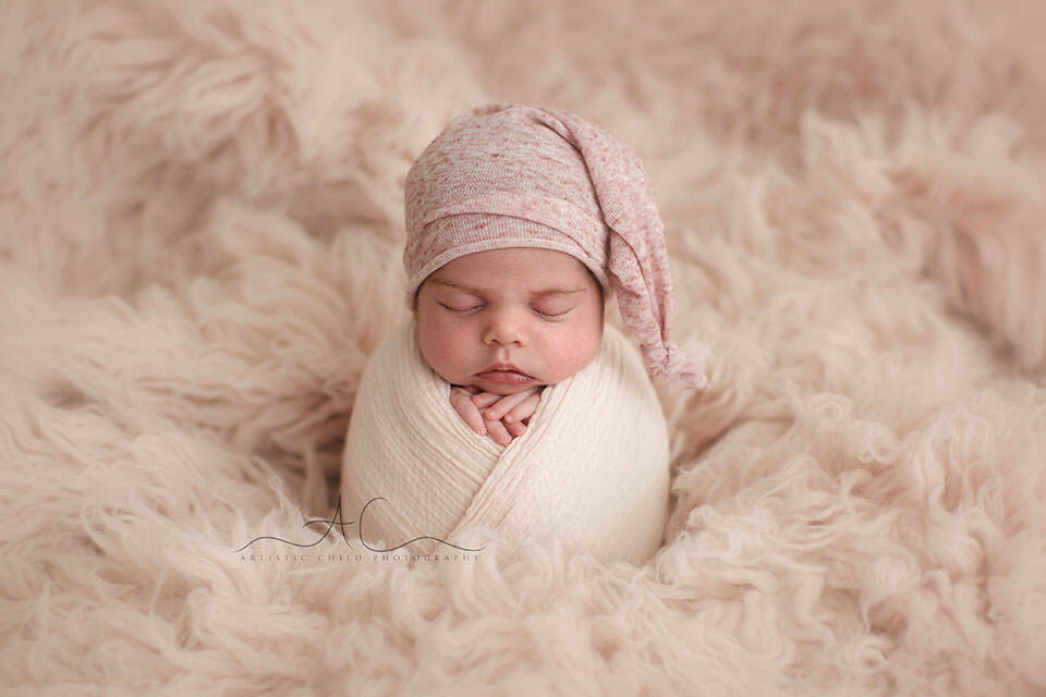 portrait of a newborn baby girl in a pink sleepy hat | London