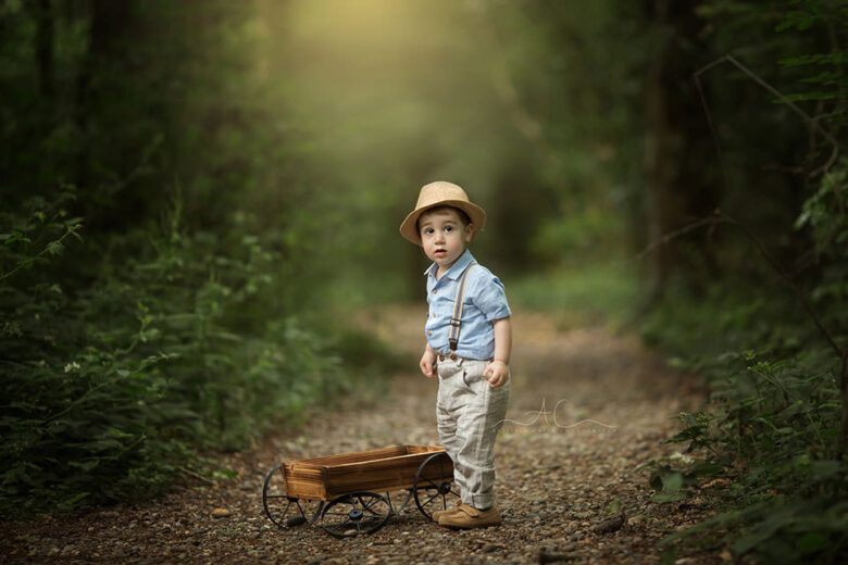 South East London Outdoor Toddler Images | portrait of a toddler boy playing with a wooden trolley in the park