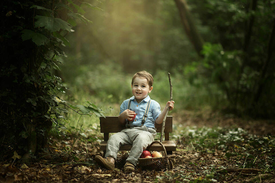 South East London Outdoor Toddler Images | photo of a toddler boy sitting on a small wooden bench in the park