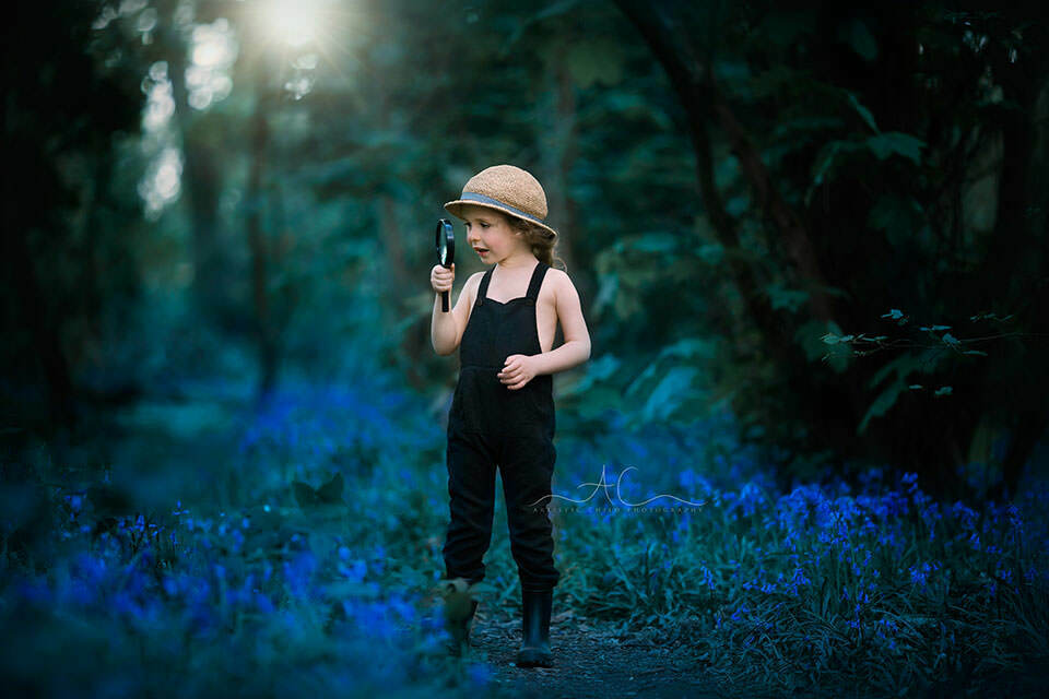 4 year old boys looks through magnifying glass while playing in London park full of bluebell flowers